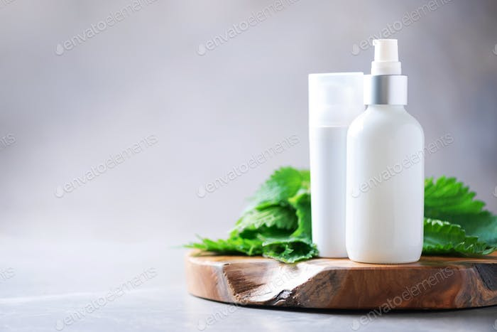 Natural spa, herbal cosmetics. Nettle lotion, cream, shampoo or soap in white bottle and fresh
