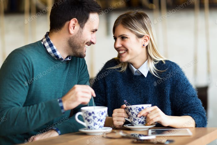 Happy young couple on date in coffee shop