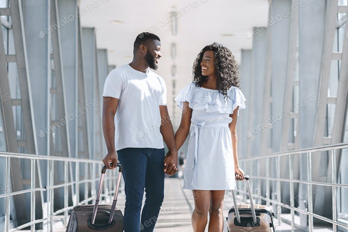 African american lovers going with luggage to vacation