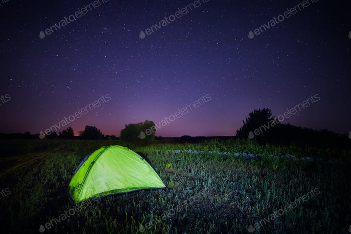 Green tent under the starry sky in the field