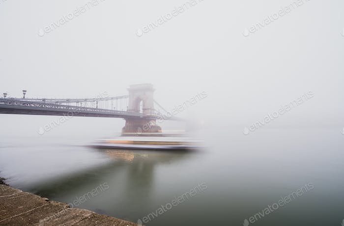 Chain Bridge over the Danube and a boat, Budapest, Hungary, in  fog, evening lights