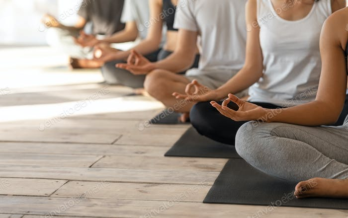Unrecognizable Group Of People Practicing Yoga In Studio, Meditating In Lotus Position