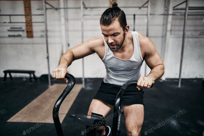 Fit young man working out on a gym stationary bike