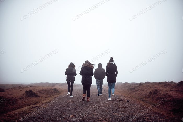 Four people hiking with fog