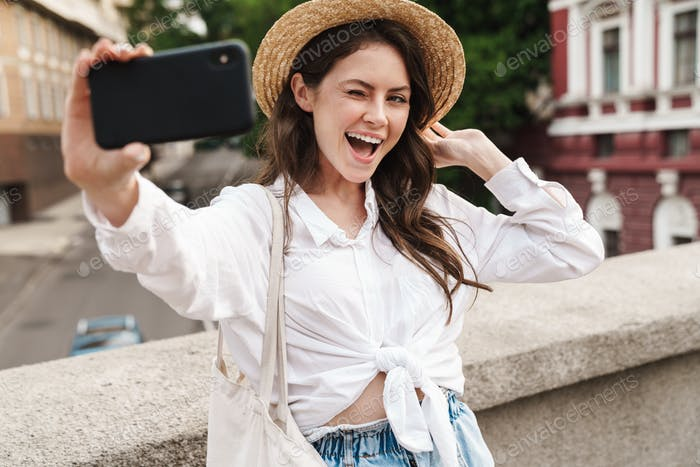 Portrait of cheerful woman winking and taking selfie on cellphone