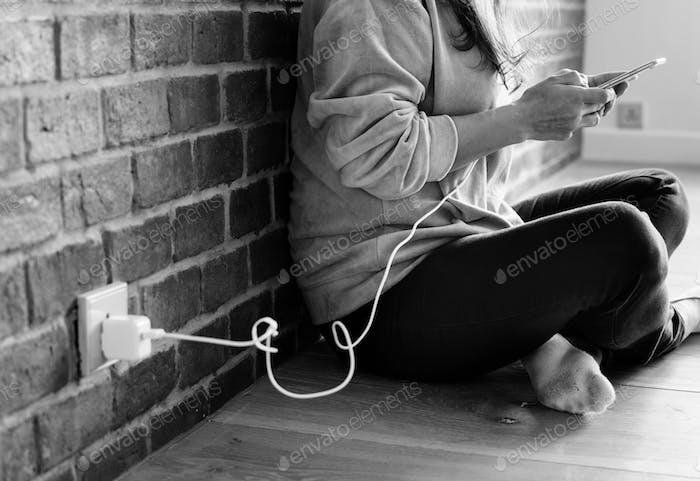 Junge Frau mit einem Smartphone, wie es aufgeladen wird