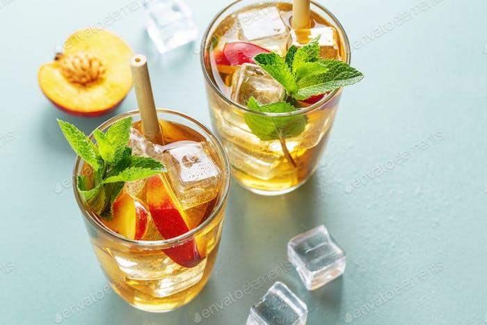 Iced tea with peach and ice cubes