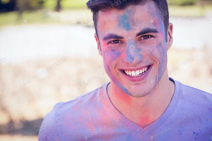 Handsome man covered with powder paint in the park on a sunny day