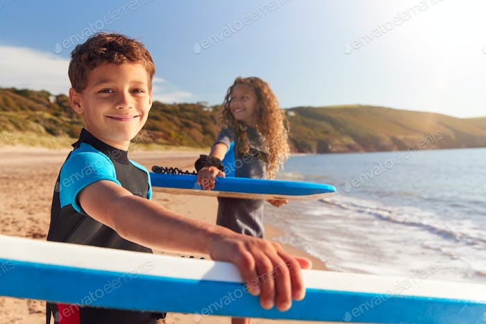 Portrait Of Children Wearing Wetsuits Carrying Bodyboards On Summer Beach Vacation Having Fun By Sea