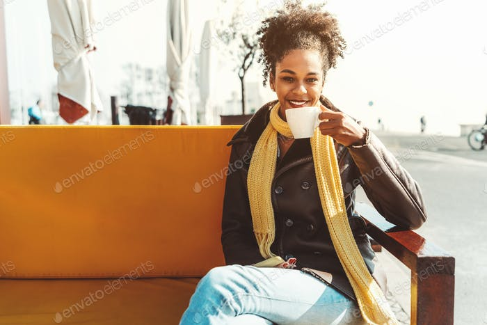 Mixed girl drinking coffee outdoors