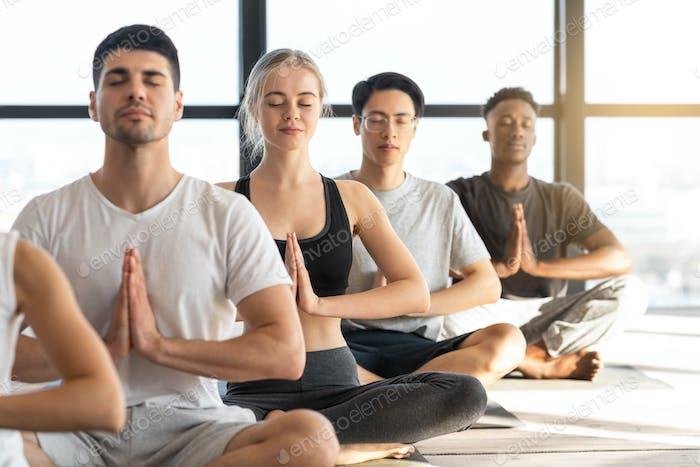 Meditationsübung. Sportliche Jugendliche, die Yoga während der Gruppenstunde im Studio praktizieren