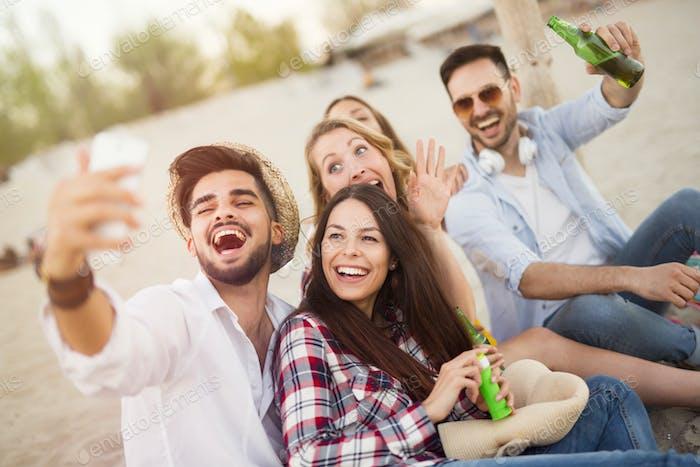 Gruppe von fröhlichen Freunden, die tolle Zeit am Strand haben