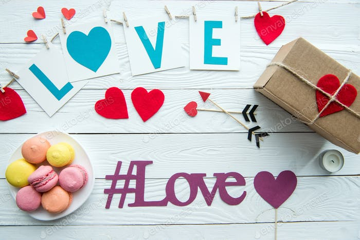 Top view of Valentines day decorations, macaroon cookies, gift box and love hashtag sign on wooden