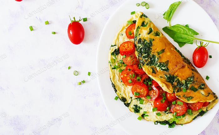 Omelette with tomatoes, spinach and green onion on white plate.