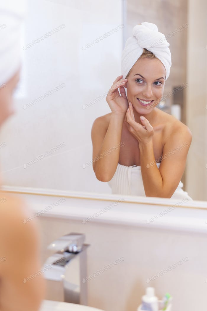 Woman looking herself reflection in mirror after the shower