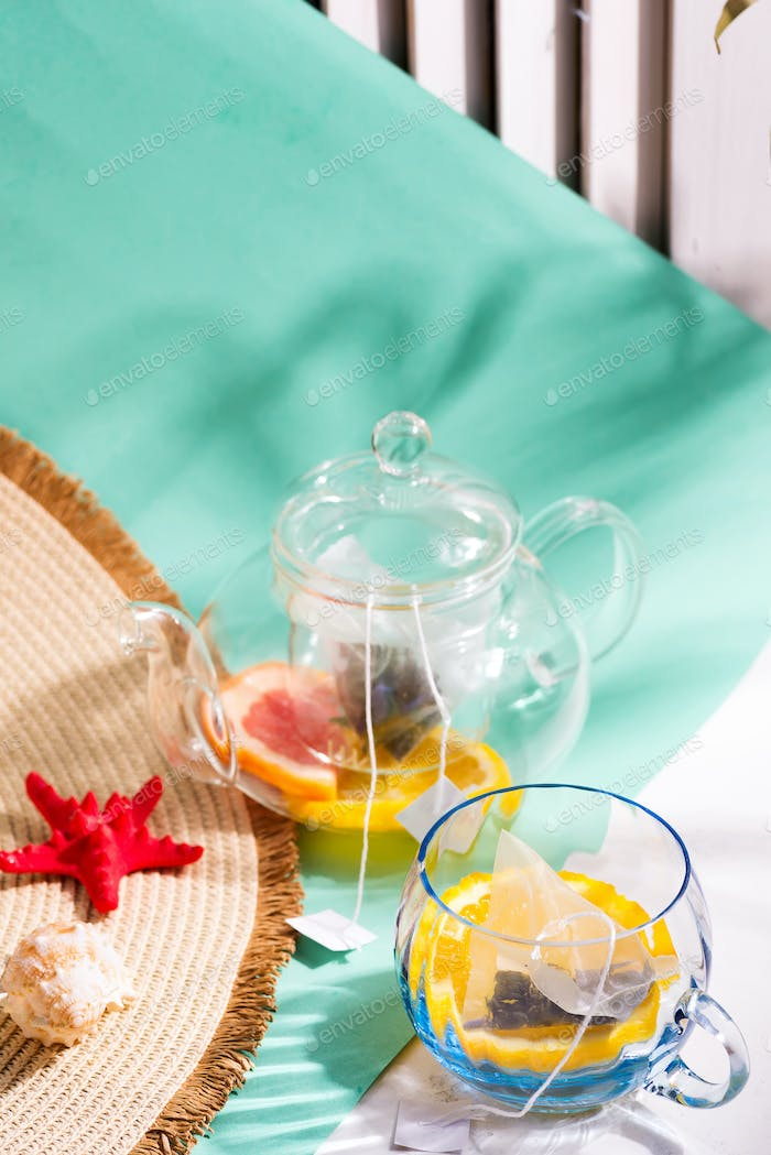 Summer layout from wide-brimmed hat and glass set with ingredients for making fresh fruit cold tea