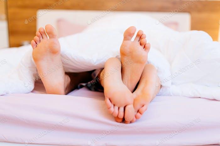 Couple having sex under blanket