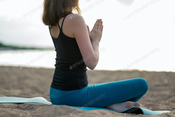 Woman doing yoga - meditating and relaxing in Padmasana Lotus Pose