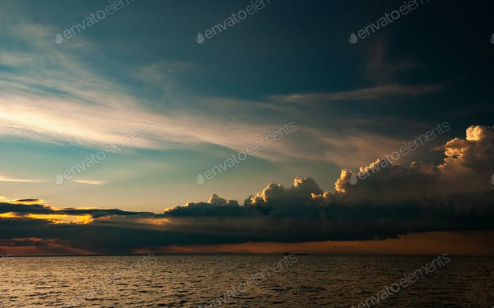 Ship crossing ocean in a sunset with sun beams, enhanced sky