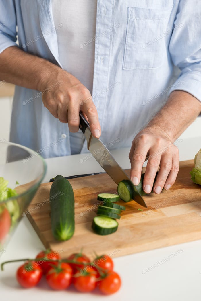 Cropped picture of mature attractive man cooking salad.