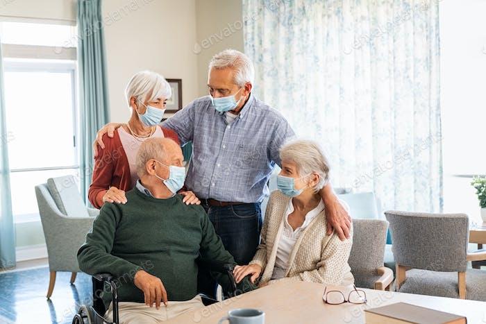 Seniors at nursing home wearing face mask and talking together