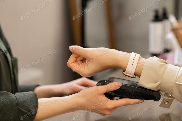 Hand of contemporary customer with smartwatch keeping wrist over pos terminal