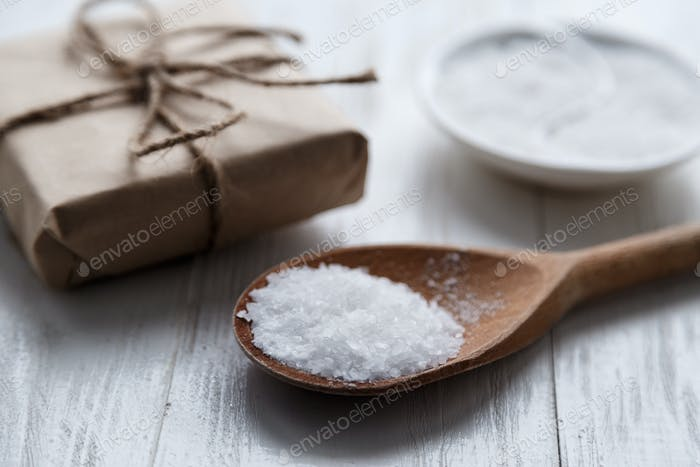 sea salt on wooden background with gift box.