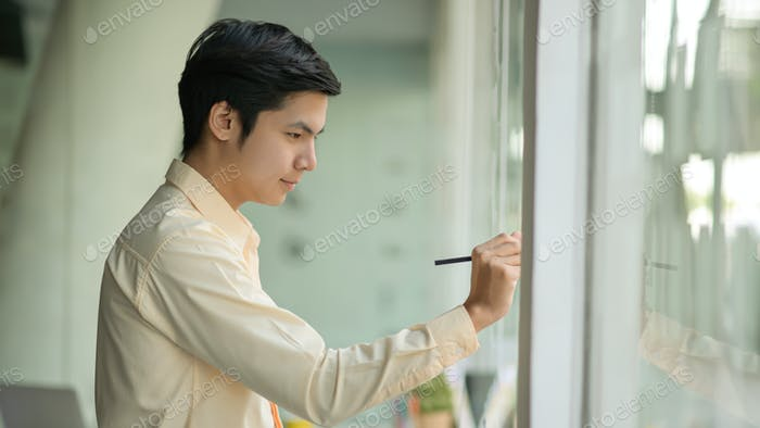 Young business man is taking notes working on a note on a glass wall in a modern office.