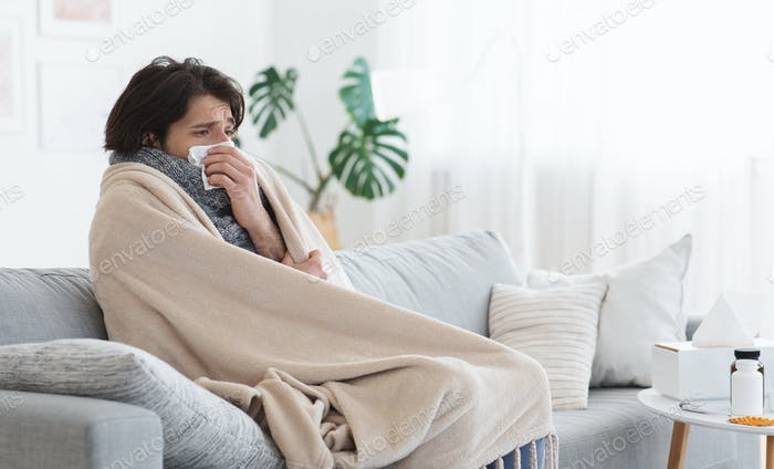 Sick man covered in blanket sneezing his nose