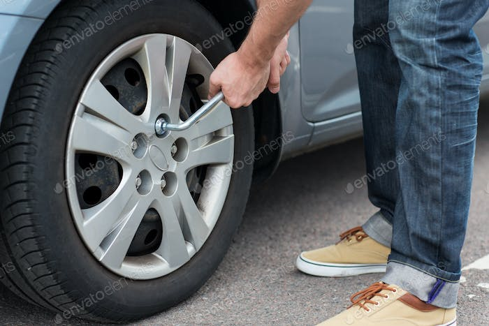 close up of man with wrench changing car tire