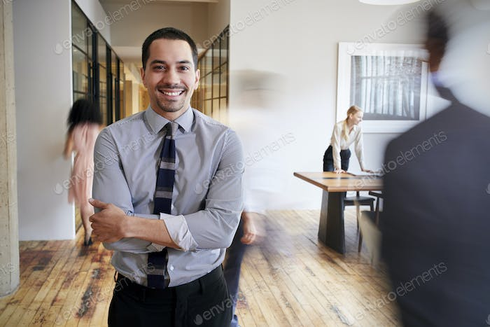 Portrait of young Hispanic man in a busy modern workplace