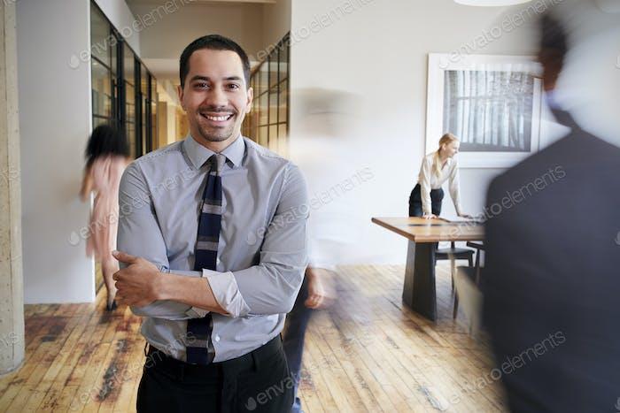 Porträt von jungen hispanischen Mann in einem geschäftigen modernen Arbeitsplatz
