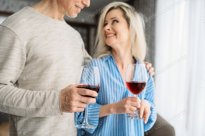 Adult love couple drinks red wine at home