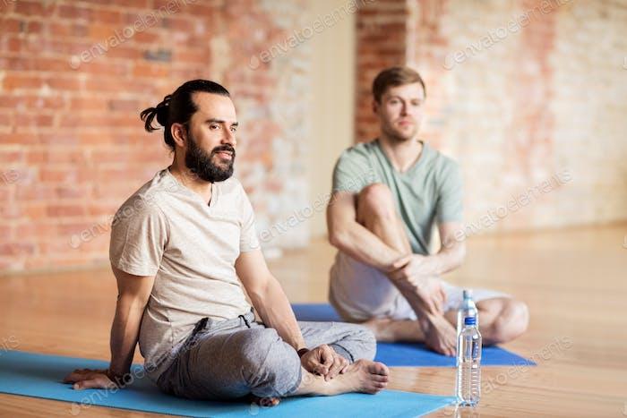 men resting on mats at yoga studio