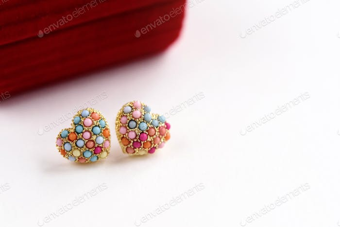 stylish luxury heart earrings with colorful gems on white background