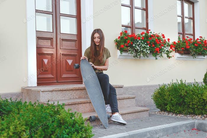 Stylishly dressed woman sitting on the steps with longboard in the hands in front of the house.