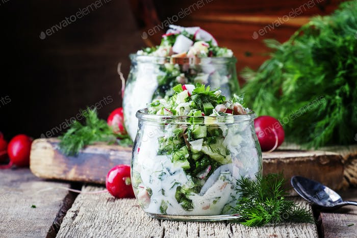 Summer cold soup with vegetables, herbs and yogurt in glass jars, rustic style