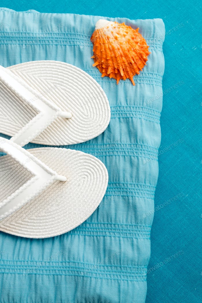 White flip flop near seashell