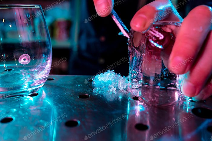 Close up of barman crushing a big piece of ice on the bar counter with a special bar equipment on it