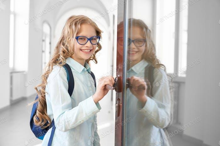 Happy blonde school girl holding opened door