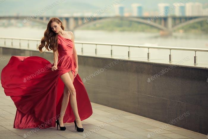 Schöne Frau In Rot Flattern Kleid. Urbaner Hintergrund.