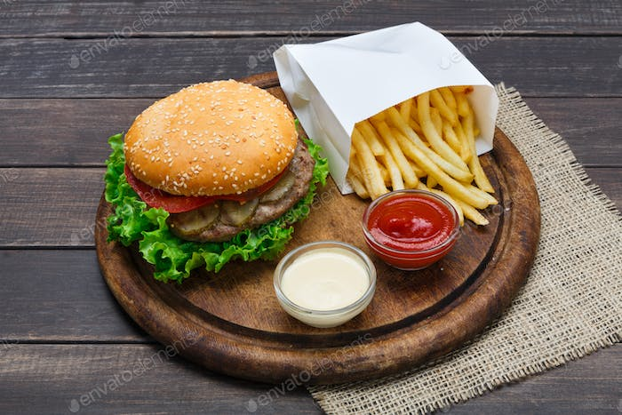Fast food take away. Hamburger and fries on wood
