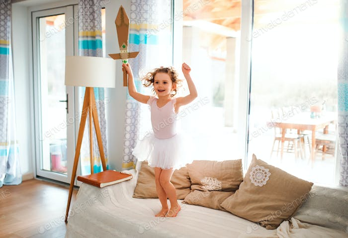 A small girl with a princess dress at home, holding a toy sword and jumping.