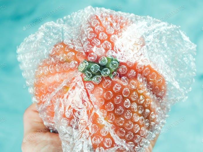 Tomate in Plastikverpackung auf Türkis