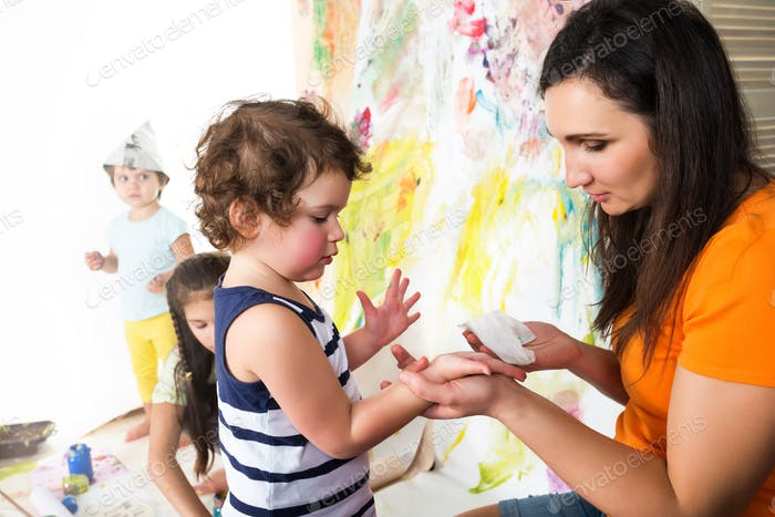 Woman and babies drawing while sitting at table