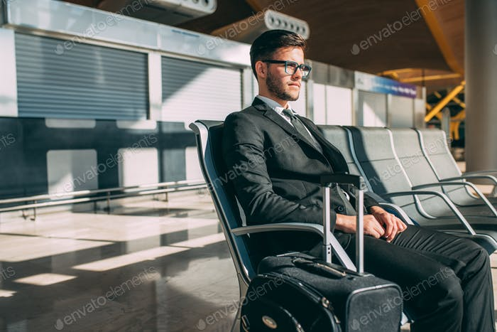 Young business man sitting at the airport waiting for the flight
