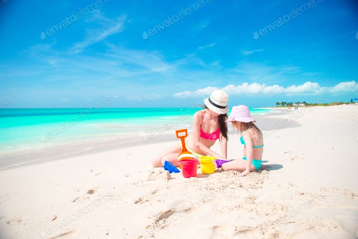 Mom and little cute baby making sandcastle at tropical beach