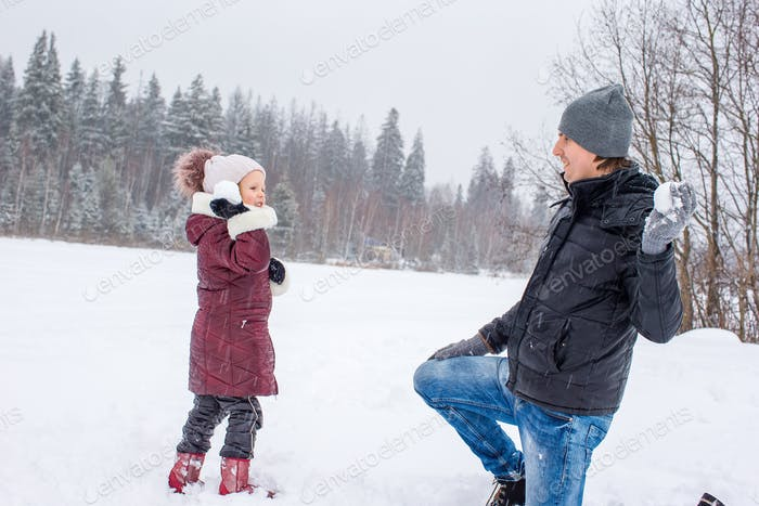 Happy family of dad and kid enjoy winter snowy day