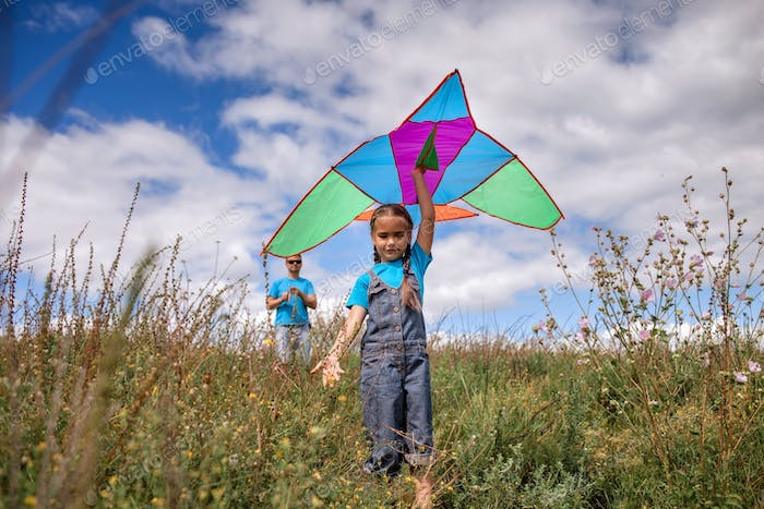Happy childhood and summertime. Kid and father playing with a kite, outdoor