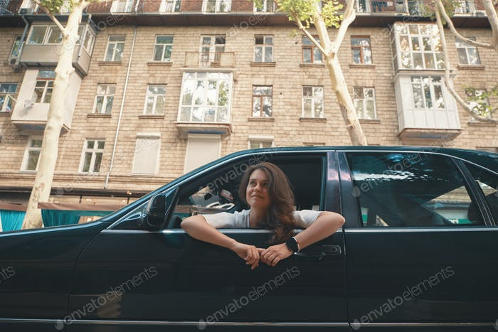Relaxed woman on city road trip travel leaning out car window